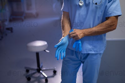 Mid section of a Caucasian male surgeon putting on rubber gloves at the hospital