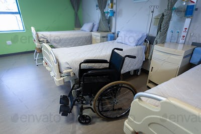 Front view of row of empty hospital beds and wheelchair in hospital