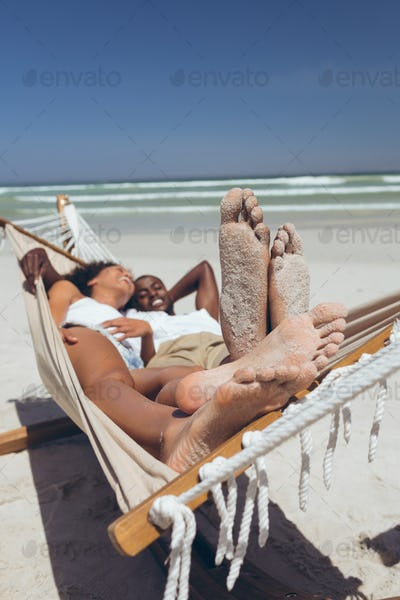 Happy young couple relaxing on hammock at beach on sunny day. They are smiling