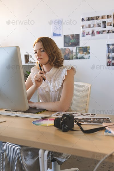 Young female graphic designer working on graphics tablet and computer at desk in the office