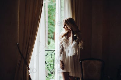 Gorgeous bride standing near balcony and looking in big window