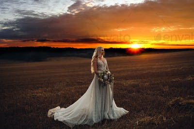 Beautiful bride posing in field at sunset time