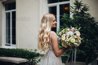 Gorgeous bride with wedding flowers boquet posing outdoors, against luxury house