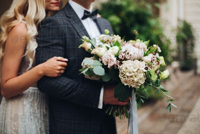 Elegant couple of blondie bride and stylish groom embracing and holding flowers