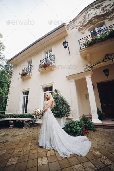 Bride in perfect wedding dress posing against luxury house with wedding boquet