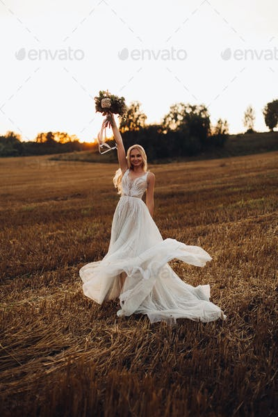 Blonde bride holding colorful wedding bouquet up