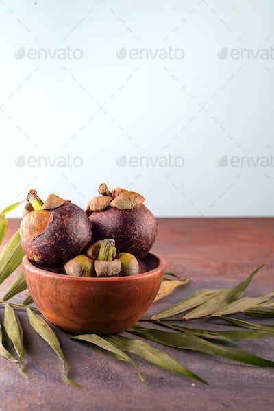 Mangosteen fruit on bamboo bowl on stone background