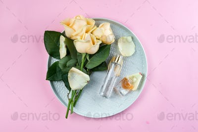 perfume bottles surrounded by rose flower on plate on pink background, flat lay