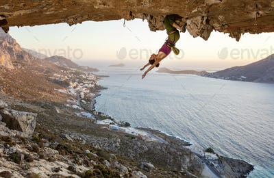 Female rock climber resting while hanging upside down