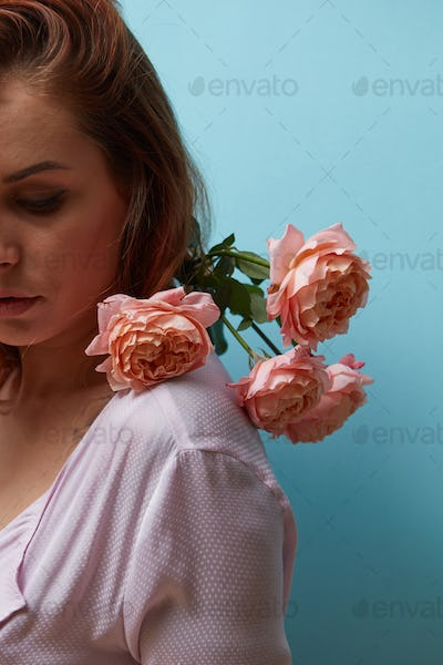 Red-haired girl with fresh pink rose decorating shoulders around the blue background with copy space
