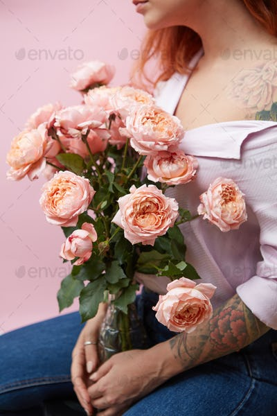A glass vase with delicate pink roses holds a girl with a tattoo around a pink background with space