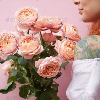 A young girl with a tattoo is holding a bouquet of elegant pink roses around her pink background