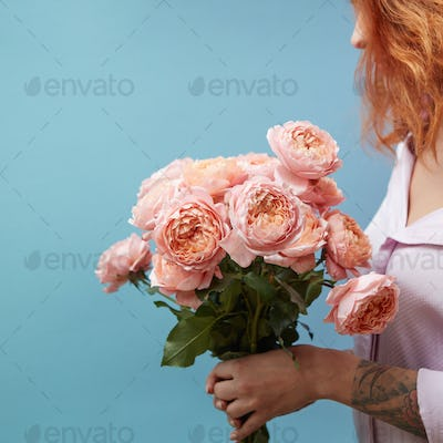 Gentle pink roses in the hands of a girl with a tattoo on a blue background with copy space for text
