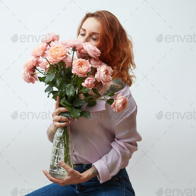 Sexy girl with a bouquet of delicate pink roses in a transparent vase on a gray background with copy