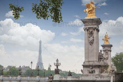Golden monuments on the bridge Pont Alexander III bridge in Paris overlooking the background the