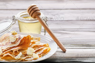 French crepes with butter and honey in ceramic dish on wooden ki
