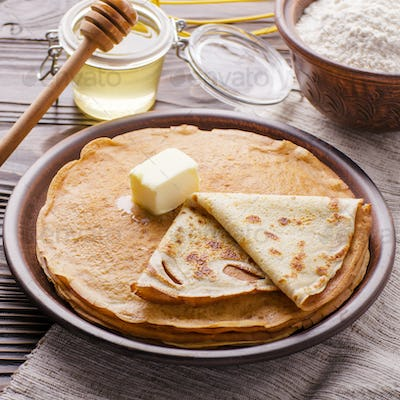 French crepes with butter flour and honey in ceramic dish on woo