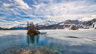 Engadine Valley. Spring thaw with islet on the lake