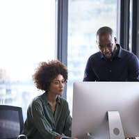 Young black male and female colleagues working together at a computer in a creative office, vertical