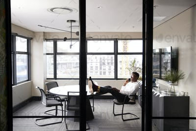 Millennial black businessman talking on the phone with feet up on a desk, seen from doorway