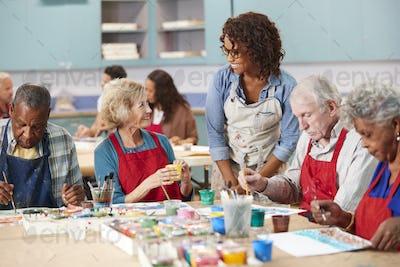 Group Of Retired Seniors Attending Art Class In Community Centre With Teacher