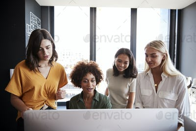 Four female creatives working around a computer monitor in an office, front view, close up