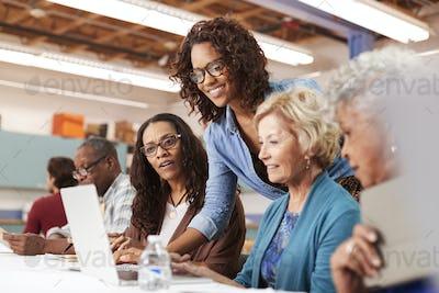 Teacher Helping Group Of Retired Senior Women Attending IT Class In Community Centre