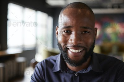 Mid adult black male creative sitting in an office dining area, head and shoulders close up
