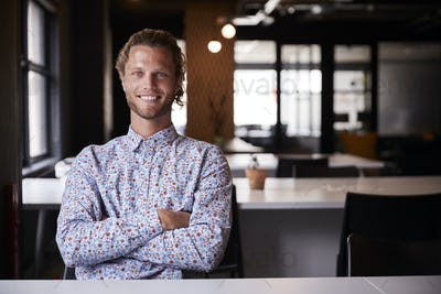 Millennial white male creative sitting in an office with arms crossed smiling to camera, close up