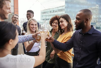 Creative business colleagues raising glasses and making a toast with drinks after work