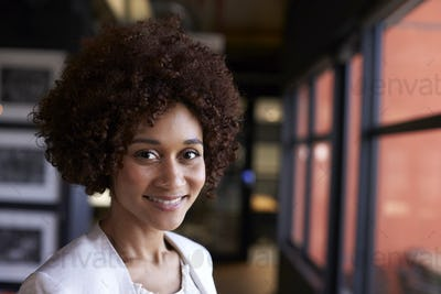 Millennial black businesswoman smiling to camera by the window in an office, close up