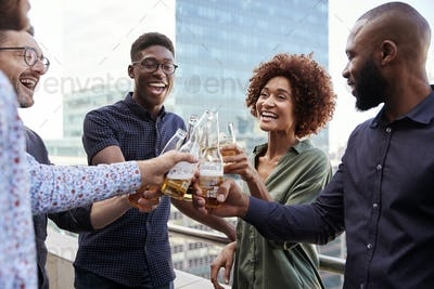 Smiling creative business colleagues drinking after work raising glasses to make a toast