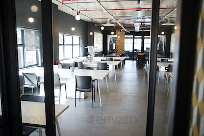 Dining area in the office of a creative business, seen from doorway in daylight, no people