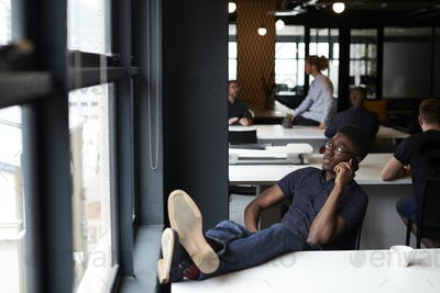 Young black male creative sitting in an office with his feet up on the desk using phone, close up