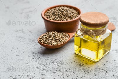 Hemp oil and hemp seeds on concrete background