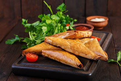 Asian food. Samsa (samosas) with chicken fillet and cheese on wooden background.
