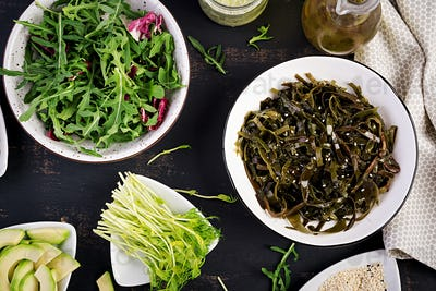 Seasoned seaweed salad and fresh herbs. Top view. Table setting