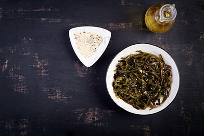 Seasoned seaweed salad and fresh herbs. Top view. Table setting
