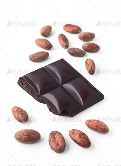 piece of bright black chocolate and whole cocoa beans, isolated on white background