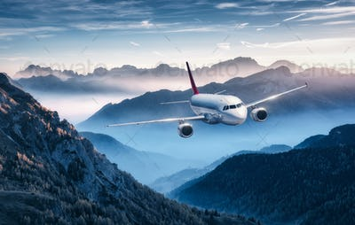 Airplane is flying over mountains in fog at colorful sunset
