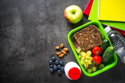 School lunch box and stationery on black background