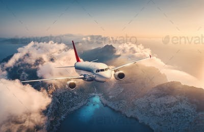White airplane is flying over mountains and low clouds