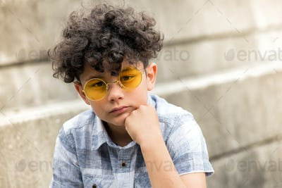 Serious young boy in yellow sunglasses