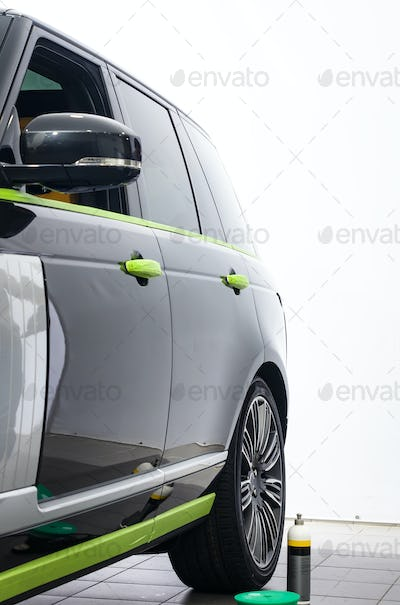 Car in applying green protective tape before polishing