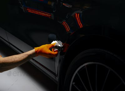 Car polish wax worker hands polishing car