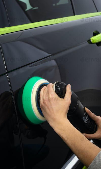 Polishing black car with a polishing machine
