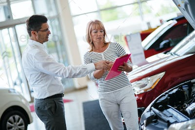 Dealer showing a new car model to the potential customer