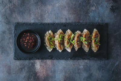 Japanese gyoza dumplings on black stone plate, copy space