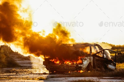 Car Burning with open flames and sunset in background