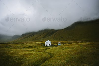 House in the middle of field in Faroe islands, with misty mountain range in the background